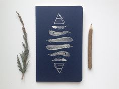 Stay organized with this hand-letterpressed Feathers & Pyramids Pattern journal! This is a navy, cahier Moleskin journal that has been printed on