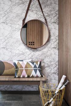 Kleine Räume mit einem Spiegel größer wirken lassen #spiegel #kissen #wandspiegel #sitzbank #mustertapete #runderspiegel #holzpaneel #papierkorb