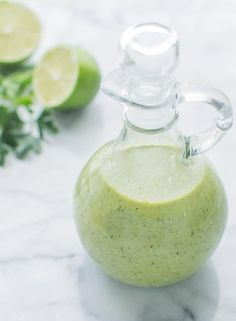 A glass bottle filled 2/3 of the way up with the creamy cilantro lime dressing. There is a lime cut in half and silantro in the background, and the bottle is on a marble countertop.