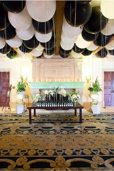 Create an impressive yet affordable reception entrance by covering the ceiling with giant balloons!  Limiting the colors to black and white keeps the look chic and from veering into children's birthday territory. Bonus points if you include a table with edible escort cards.