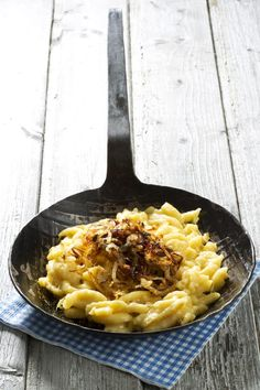 Homemade traditional Käsespätzle or cheese spaetzle. A German comfort food recipe using homemade german noodles, cheese and topped with caramelized onions