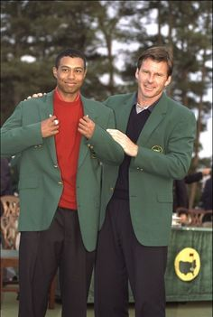 : 1996 US Masters winner Nick Faldo of Great Britain presents Tiger Woods of the USA with the winners green jacket after Woods won the 1997 US Masters tournament at Augusta with a record low score of 18 under par