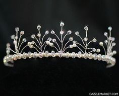 Idelle is a beautiful tiara handcrafted with sparkling Swarovski Crystal and lustrous ivory cream imitation pearl woven on silver plated wire and set on a silver tone tiara band.