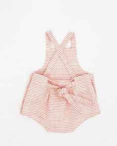 wolfechild signature sunsuit features a square bib neck, pleated bottom detail, criss crossing straps tie at center back and buttons up sides. line...