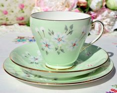 Royal Grafton Studio Craft vintage bone china teacup, saucer and tea plate trio. c.1957+ A pale green body with stylized white flowers hand painted with blue markings, enamelled red centres and taupe and grey foliage. Smooth gold gilded rims, teacup handle and base. Footed teacup 9.25cm wide at the rim x 7.5cm tall. 14cm wide Saucer and 16cm wide Tea Plate. Royal Grafton Studio Craft made by A.B.Jones, Grafton Works, Longton, Staffordshire, England. c.1957+ In excellent condition.
