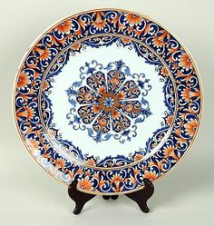 """Large Rouen faience charger,18th/19th century, with radiating floral medallion and floral border in blue and orange. 14 3/8"""" diameter."""