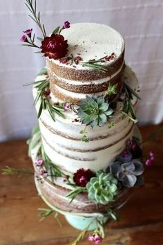 Stunning three tiered naked cake accented with burgundy, purple, and green earthy tones.  The combination of greenery, flowers, and succulents make for a rustic, organic wedding cake.