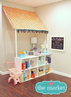 So You Think You're Crafty: The Market She created the canopy out of Ikea fabric, PVC pipe frame, and added a cute little banner made out of chalkboard fabric.  Below the canopy is a cubby unit turned on it's side, which provides lots of shelving for all of the play food they need.