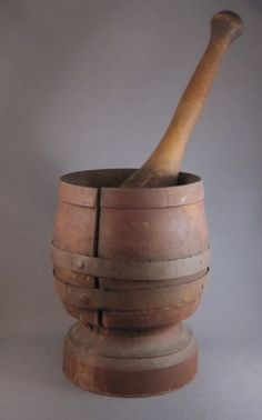 Wooden mortar & pestle, c.1850-75 - Large American primitive lathe-turned treenware mortar (with original red painted surface) & pestle. It was not unusual for wooden utilitarian items such as bowls and mortars to crack, due to a change in climate. Two steel bands were added to help stabilize the large break.