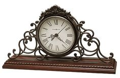 "The Howard Miller Adelaide 635-130 Mantel Clock is an ornate chiming mantel clock that features a sculpted wrought iron frame with decorative cast crown, antique warm grey finish, and sits on a Windsor Cherry finished base. Decorative molding runs completely around the base. Beneath a convex glass crystal, the antique finished serpentine hands are complemented by the aged dial and black Roman numerals. Quartz movement plays Westminster melody on the hour. Size: H. 9"" W. 15-1/2"" D. 4"""