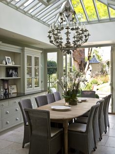 Soft grey green walls with dark grey accents... Modern Country conservatory dining room... and I spy a lollipop tree outside too!