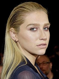 Kesha's slicked back hairstyle with bold eyebrows and matching ballet-pink eyeshadow and lipstick | allure.com