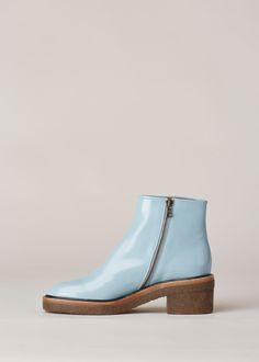 """Ankle boot in shiny powder blue leather. Exposed zip closure along inner ankle. Rounded toe. 2.5"""" chunky heel and sole in tobacco rubber crepe. Branded dust bag included."""