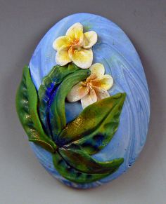 "This is a cabochon! I created it during a ""Painterly Polymer"" class I taught recently in Brisbane, Australia. These are frangipani blooms, and they are one of my most favorite flowers (and trees) found in tropical places! #art #cabochon #polymer #frangipani #ChristiFriesen"
