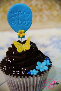 "This is really cute idea! Brown color baby shower cupcake with yellow butterfly , small blue flowers, little white sprinklers and a small ballon with ""It's a Boy"""