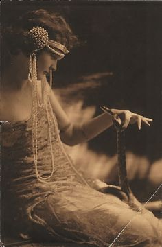 receivethesound:    My great grandmother Dagmar, holding eyes with a snake. Date unknown, probably mid twenties.!