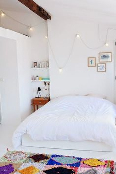 All White Bed, Boho Bedroom, cafe lights bedroom, flukati rug, minimal white bedroom, queen size bed stylish, pop of color bedding, colorful geometric rug, white bedroom inspiration