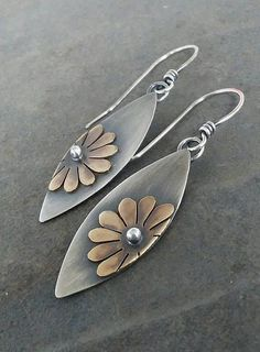 I made this beautiful pair of daisy earrings by hand using sterling silver and brass. Each piece is hand cut by me using sterling silver and brass and is soldered in place. This pair measures 2 1/8 inches in length from the top of the ear wire to the bottom of the dangle. They have been