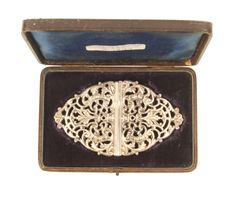 A ladys silver waist buckle, in original case, each half pierced with leaves and scrolls, Birmingham 1899, by Latham and Morton