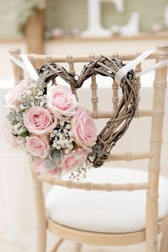 Add pink flowers to wicker hearts for wedding chair baaks - this is a lovely idea if you are looking for pink wedding decorations