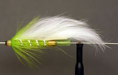 """River Zonker This fly works particularly well on the """"Big"""" river. Tube: Brass or Copper Rib: Oval silver tinsel. Body: Chartreuse dubbing dressed thin. Wing: White rabbit strip tied down to the body matuka style with the rib. Hackle: Chartreuse. Head: Yellow"""