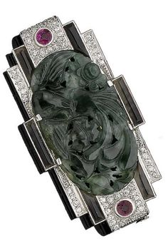 An Art Deco jade, ruby, agate and diamond brooch, circa 1925. The oval jade plaque carved to depict a phoenix, symbol of renewal and immortality, within a geometric surround of banded agate, circular-cut rubies and old brilliant-cut diamonds, cased by J. E. Caldwell. #ArtDeco #brooch