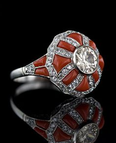 Buff-Cut Ox-Blood Coral and Diamond Set Platinum Channels in an Art Deco Ring.