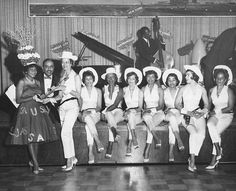 Ride'Um Cowgirls | 1962  A photograph of a night club featuring; nine girls dressed in a western motif, band members, and tenth woman dressed slightly more formally receiving a trophy, May 1962. Charlotta Bass/California Eagle Photograph Collection, Southern California Library for Social Studies and Research, Los Angeles, CA