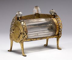 "This barrel-shaped reliquary consists of a large, cylindrical piece of crystal bored down the middle to create a narrow compartment for a relic.     According to medieval lapidaries, rock crystal was a symbol of spiritual purity.      The rock crystal chamber magnified the relics contained inside, establishing the real presence of the saint.    improvements in techniques for hollowing rock crystal made possible the production of these ""roll"" reliquaries."