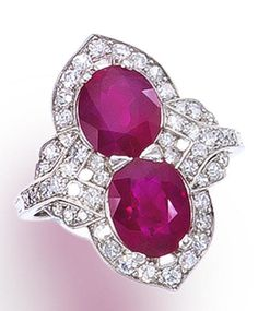 A ruby and diamond two-stone ring  set with two oval-shaped rubies, surrounded by single-cut diamonds in an openwork mount with millegrain accents; rubies weighing approximately 2.05 and 1.75 carats;