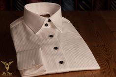 White bespoke shirt with fancy stripes and black buttons and double cuffs.