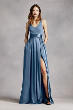 V-neck halter gown with matte crepe bodice features bow detail at back.  Long soft charmeuse skirt with middle slit an