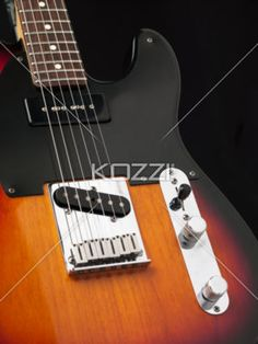 cropped image of electric guitar against dark background. - Close-up cropped shot of a electric guitar with metal strings and volume knobs against dark background.
