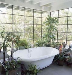 fabulous bathroom with huge houseplants, freestanding bath and crittal black windows