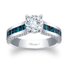 Modern, straight lines, and clean styling permeate in this unique blue and diamond engagement ring with a prong set round diamond center.  A channel of blue princess cut diamonds cascade down the shoulders and pave set diamond grace the sides for a stunningly elegant touch of sophistication.