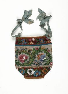 A bag covered in fine glass beads in a brightly coloured floral design, the lining is of cream silk. Circa 1830s.