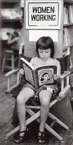 "An unidentified girl is taking some time to read Wonder Woman under a ""Women Working"" sign."
