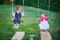 Little boy and girl ride in the park on a swing