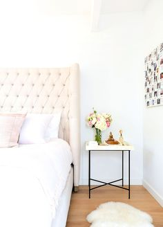 White walls, beige bed framed, white bedding, faux fur white rug, and pink throw pillow