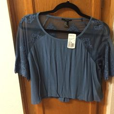 NWT Dusty Blue Crop Top NWT Dusty Blue Crop Top with beautiful sheer top and sleeves, and intricate embroidered flowers woven into the sheer fabric. Forever 21 Tops Crop Tops