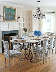 Blue and White gingham keeps this dining room from becoming too old-fashioned. Classic white #fireplace. Design by Sallie Giordano.