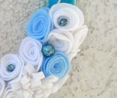 A snow covered winter felt and yarn wreath with blue butterfly.