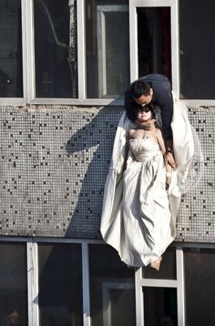 In this photo taken Tuesday, May 17, 2011, a cadre of the community office grabs 22 year-old woman after she tried to kill herself by jumping out of a window of a seventh floor building in Changchun city in northeastern China's Jilin province. The bride surnamed Li cut her wrists and tried to commit suicide after her boyfriend broke up with her just before the marriage.