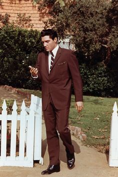 Rock and roll singer Elvis Presley walking through a white picket fence in circa 1957 in Memphis, Tennessee.