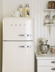 I love this whole image. Smeg fridge, stand mixer, cream decor and the vintage enamel thermos flasks.