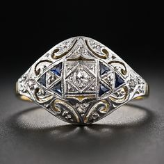 A very lovely early-twentieth century Art Deco cigar band style ring delicately crafted in two-tone 18 karat gold and shimmering in the center with an old mine-cut diamond accented with six triangle synthetic sapphires (original to the ring and the period) and a teeny-tiny pair of rose-cut diamonds on the shoulders. Circa 1920s-30s.