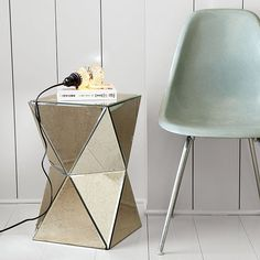 Whether you're going for old-Hollywood glamour or edgy, angular style, the Faceted Mirror Side Table's antiqued mirror surface reflects and refracts light, lightening up the look of any room.