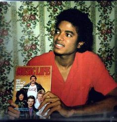 Michael Jackson holding a magazine featuring Queen on the cover
