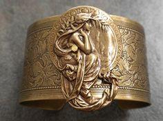 Art Nouveau cuff - ornate floral design, featuring a draped feminine figure with long hair.
