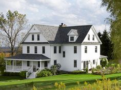 Beneath the exterior's yellow asbestos shingles, Lisa and Mark Hellman discovered well-preserved clapboard, which they painted with Benjamin Moore's Flat White. The couple also had the roof and all 57 windows replaced, and the porch torn down and rebuilt. - ELLEDecor.com